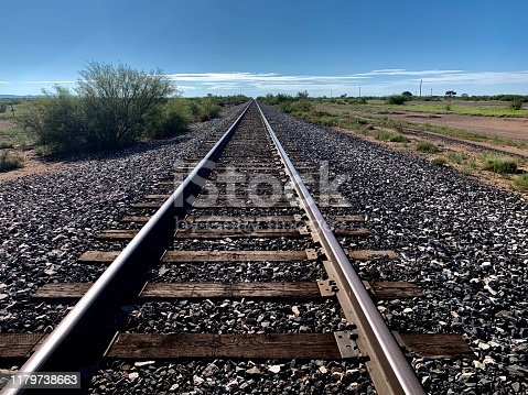 Railway track cut through the vast west Texas desert for as far as the eye can see.