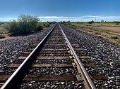 Railway track cut through the vast west Texas desert for as far as the eye can see.
