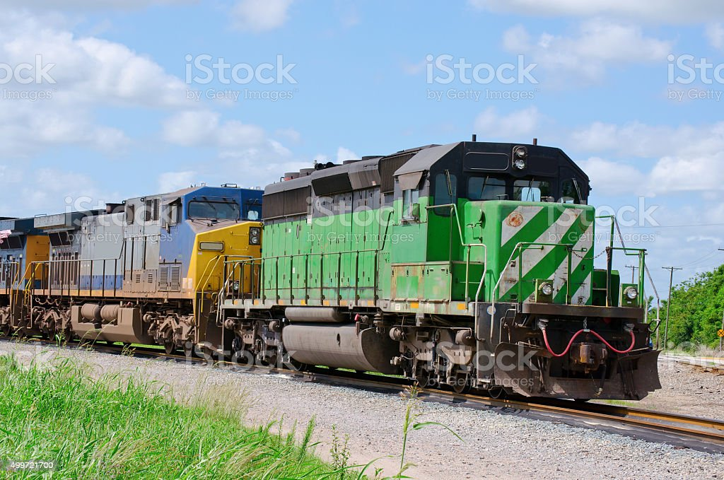 Train towing another train speeding down the track stock photo