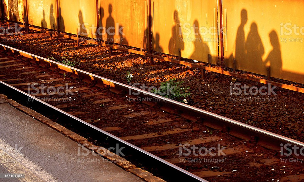 Train track with shadows of people against wall stock photo