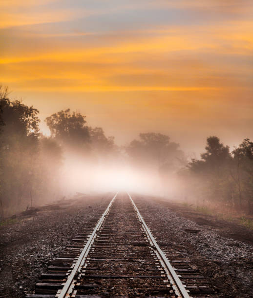 Train tracks disappear into strange glowing fog. stock photo