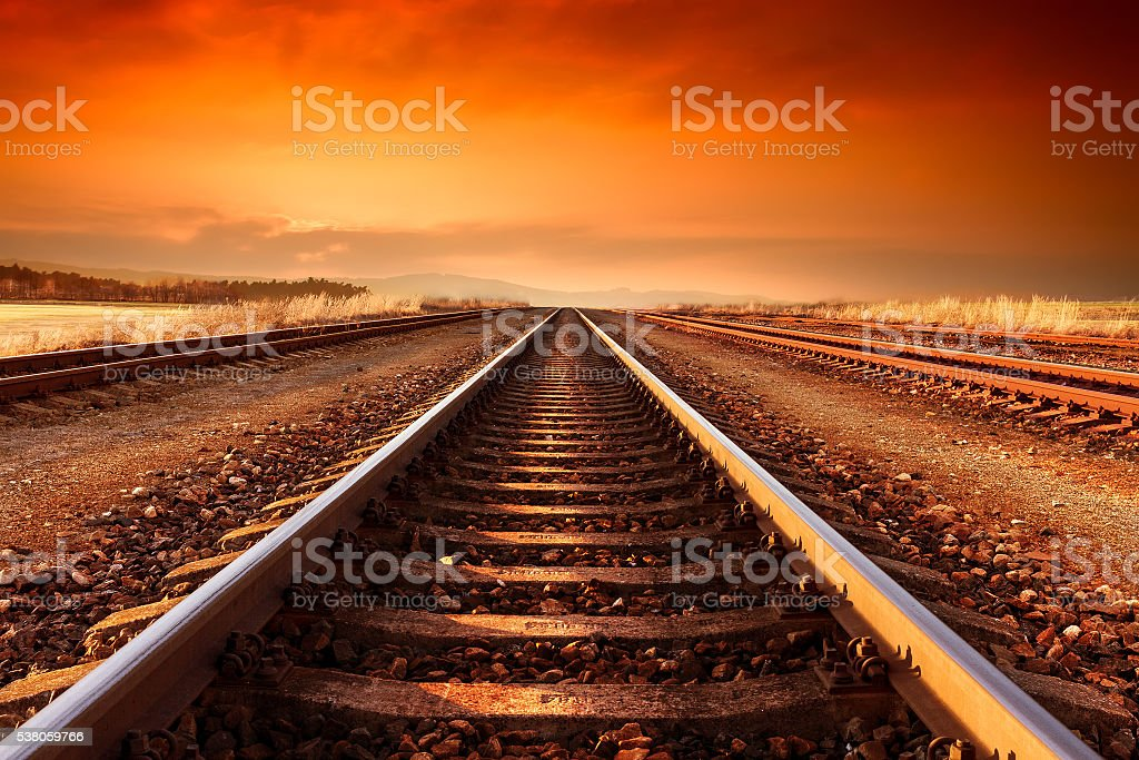 Train tracks goes to horizon in the majestic sunset. stock photo