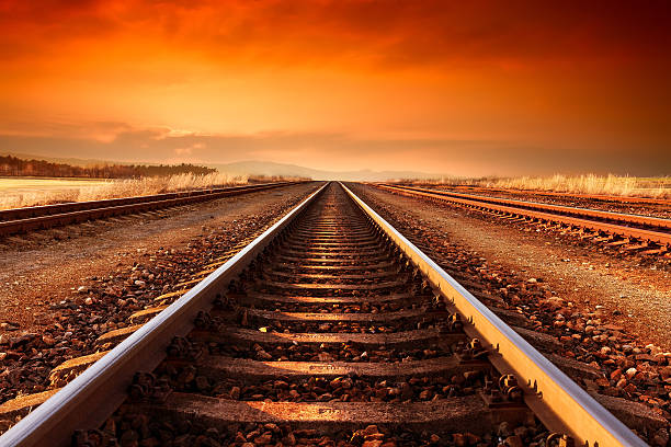 Train tracks goes to horizon in the majestic sunset. Train tracks goes to horizon in orange majestic sunset. tramway stock pictures, royalty-free photos & images
