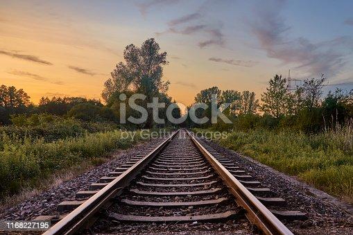istock Train tracks infront of beautiful nature and the sunset in Rastatt, Germany 1168227195