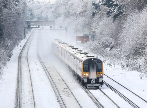Train transporting commuters in winter snow and ice to London
