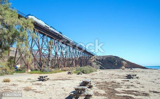 Train traveling over railroad track bridge at Gaviota Beach state park on the central coast of California United States
