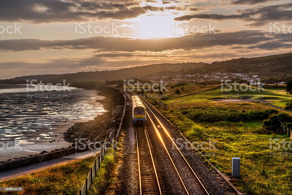 Train travelling past sea wall at sunset stock photo