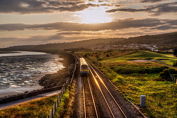 Train travelling past sea wall at sunset Train travelling past sea wall at sunset south wales stock pictures, royalty-free photos & images