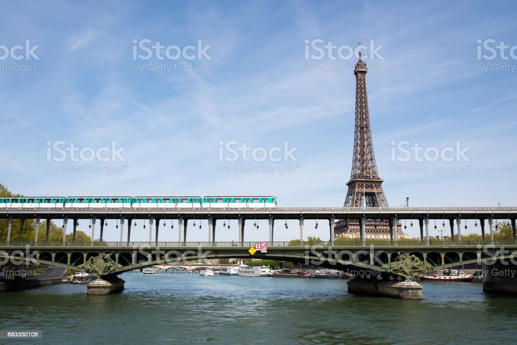 Train travels on Pont de Bir Hakeim in front of Eiffel tower stock photo