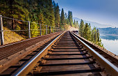 A close-up, tilt-shift view of a train trestle that rounds a curve and slowly vanishes into the distance