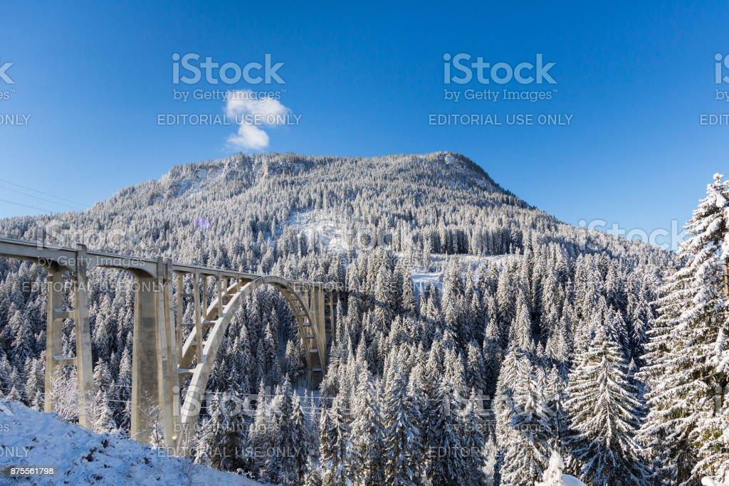 train viaduct Langwies in Switzerland in sunshine, winter, snow, blue sky stock photo