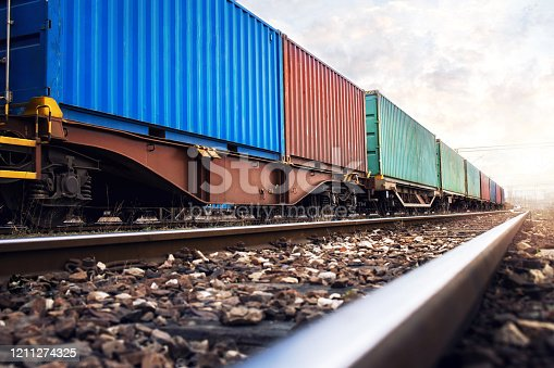 istock Train wagons carrying cargo containers for shipping companies. 1211274325