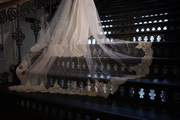 train wedding dress lying on the iron stairs - festzugskleidung stock-fotos und bilder