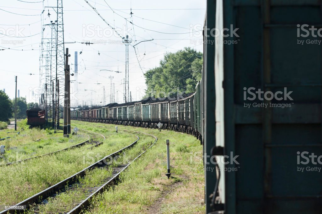 Train with coking coal cars on the background of the coke plant. stock photo