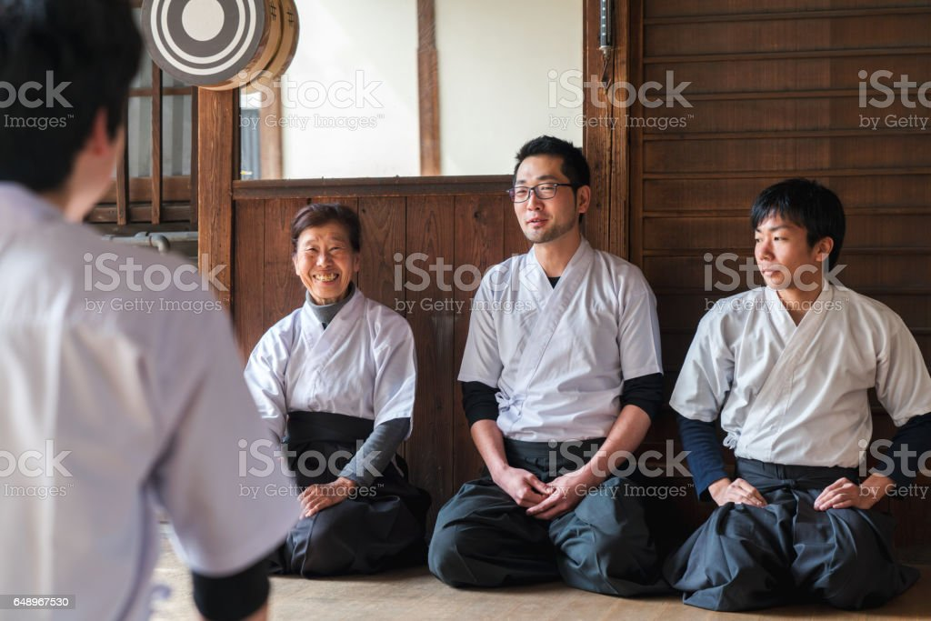 Trainee archer getting feedback from his teachers stock photo