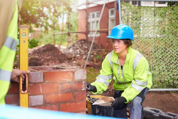 trainee bricklayer listening to her supervisor stock photo