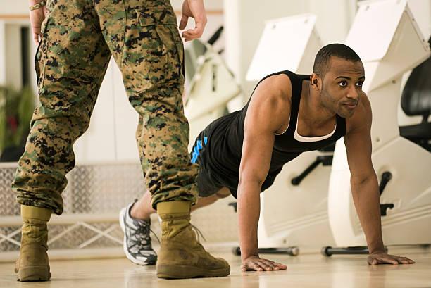 auszubildender tun burpees in einem fitness bootcamp - militärisches training stock-fotos und bilder