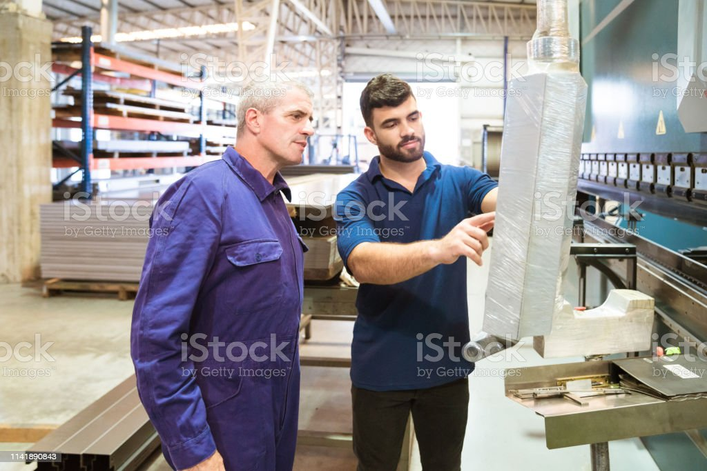 Trainee explaining engineer in industry Trainee discussing with engineer while pointing at equipment. Workers are working in industry. They are in uniforms. 20-24 Years Stock Photo