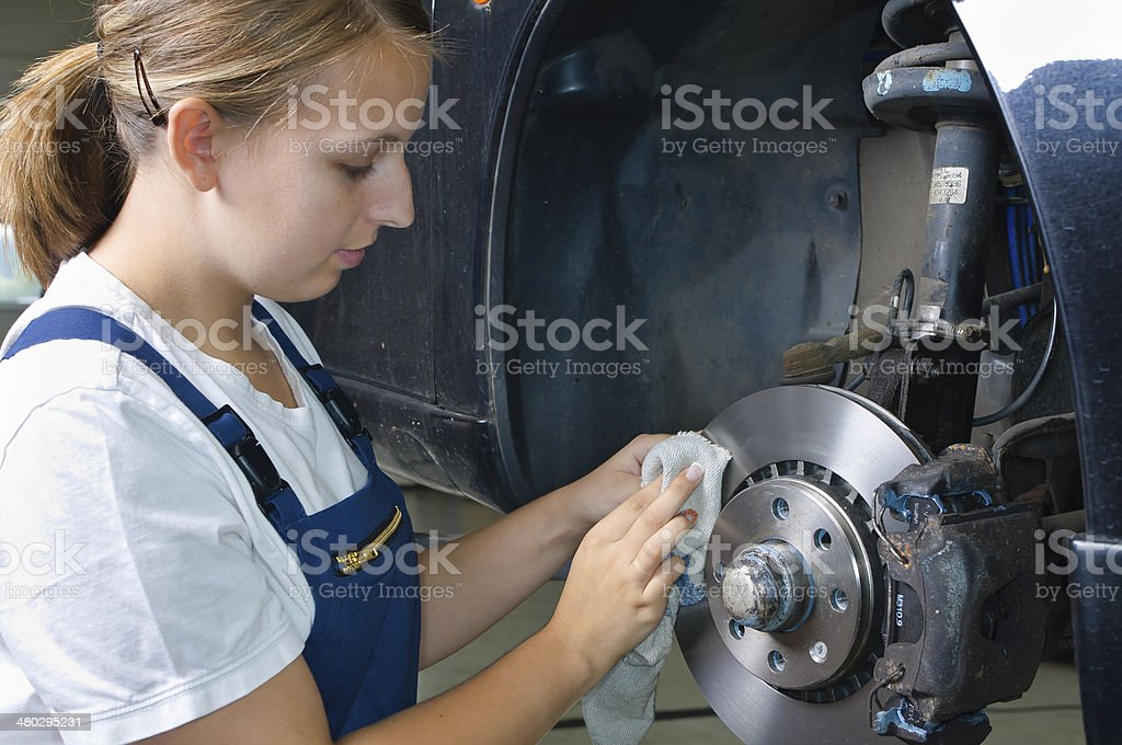 Trainee in the garage cleaning brakes stock photo