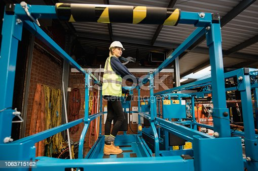 A low-down shot of a trainee mechanic standing on a cherry picker, she is wearing a protective hard hat, hi-vis jacket and warm clothing.