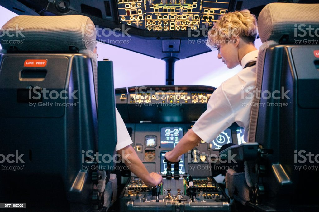 Trainee Pilot Operating Throttle In Flight Simulator With Instructor stock photo