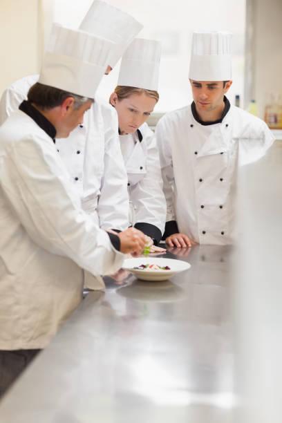 trainees listening to the head chef - kitchen counter imagens e fotografias de stock