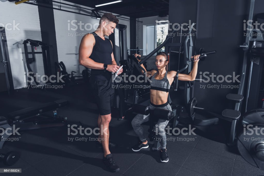 trainer and sportive woman in gym royalty-free stock photo