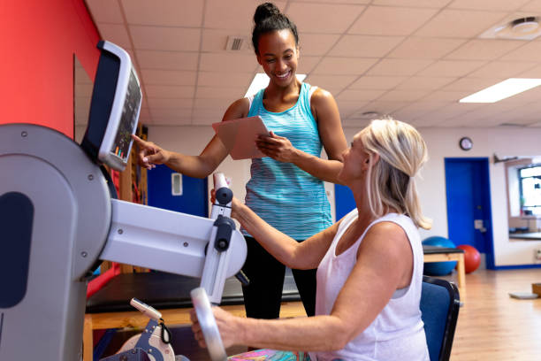 Trainer assisting disabled active senior woman to exercise in exercise equipment stock photo