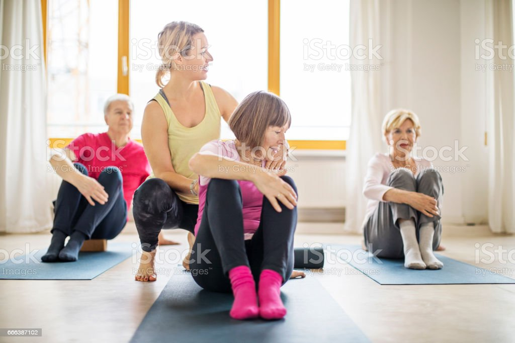 Trainer assisting senior woman in doing yoga stock photo