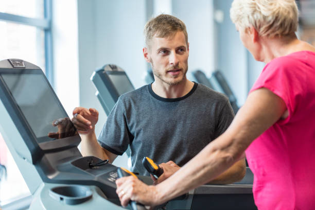 trainer coaching senior woman exercising in rehab gym - runner rehab gym foto e immagini stock