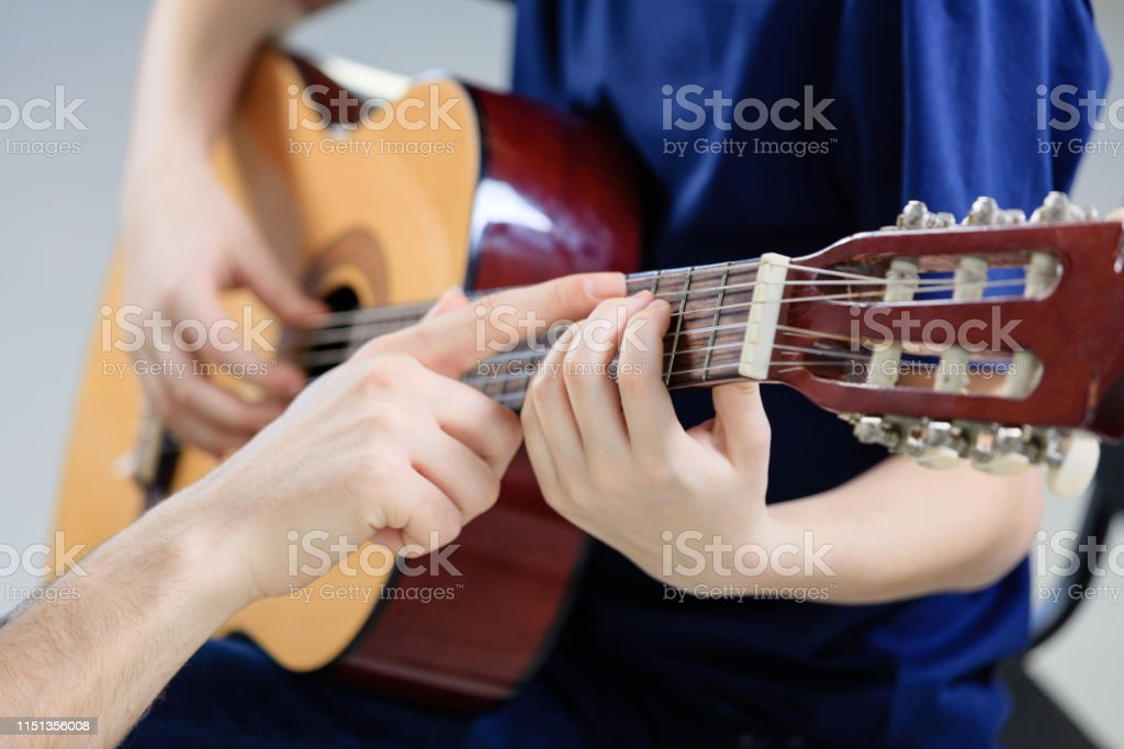 Trainer explaining guitar strings to student Cropped image of teacher explaining guitar strings to student on fretboard. Pre-adolescent boy is learning musical instrument in class. They are playing music at conservatory. 12-13 Years Stock Photo