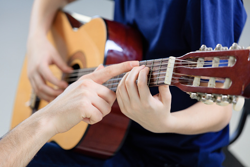 Trainer Explaining Guitar Strings To Student Stock Photo - Download Image Now