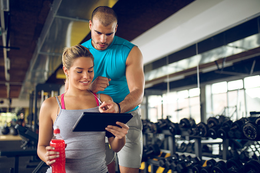 860045834 istock photo Trainer explaining workout regime to woman 874896056
