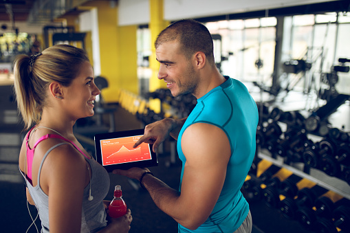 860045834 istock photo Trainer explaining workout regime to woman 874903736