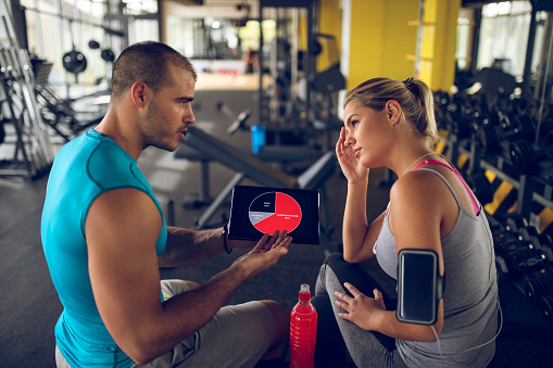 860045834 istock photo Trainer explaining workout regime to woman 874904130