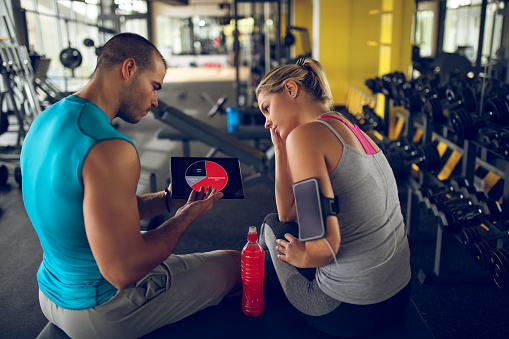 860045834 istock photo Trainer explaining workout regime to woman 882287744