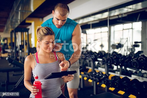 860045834istockphoto Trainer explaining workout regime to woman 942243110