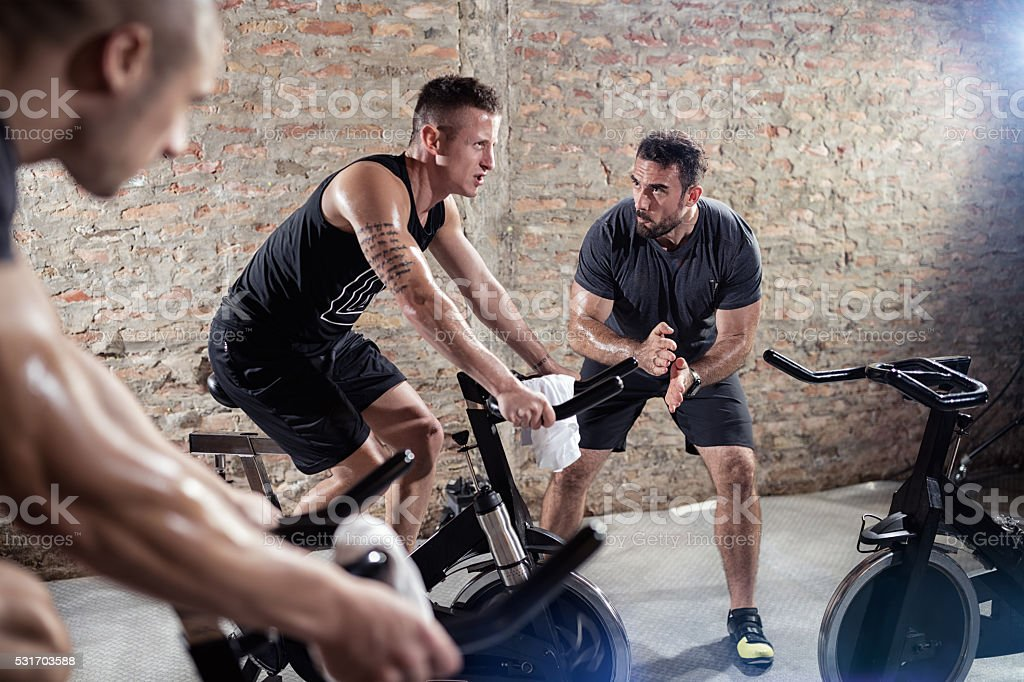trainer gives support man on a spinning training stock photo