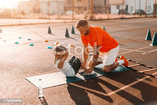 istock Trainer helping kid to do abs on the court in the morning. 1125034689
