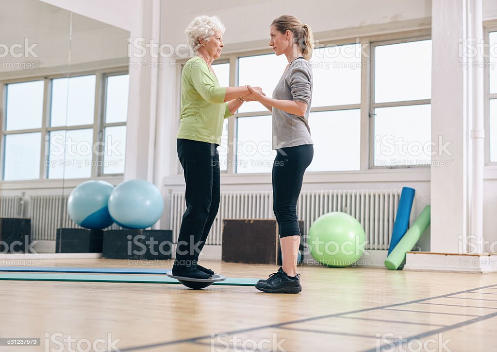 Trainer helping senior woman exercising with a bosu balance stock photo