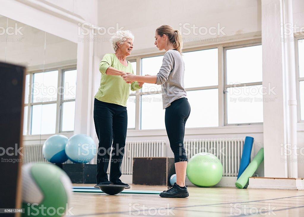 Trainer helfen senior Frau auf bosu balance-Plattform – Foto