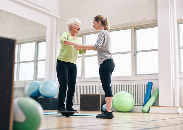 Trainer helping senior woman on bosu balance training platform stock photo