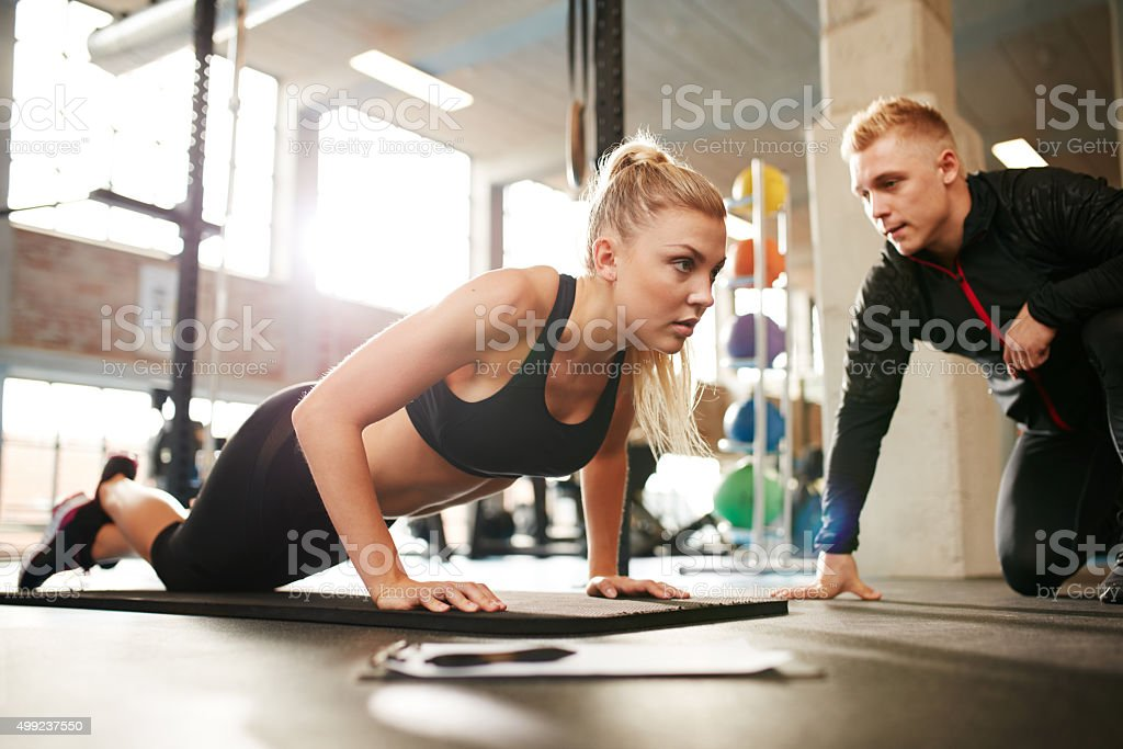 Trainer helping woman do push ups stock photo