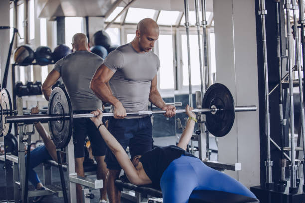 Trainer helping woman in gym stock photo
