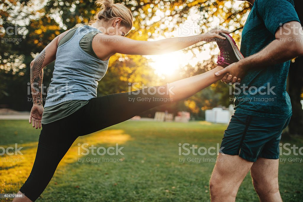 Trainer helping woman in leg stretching workout stock photo