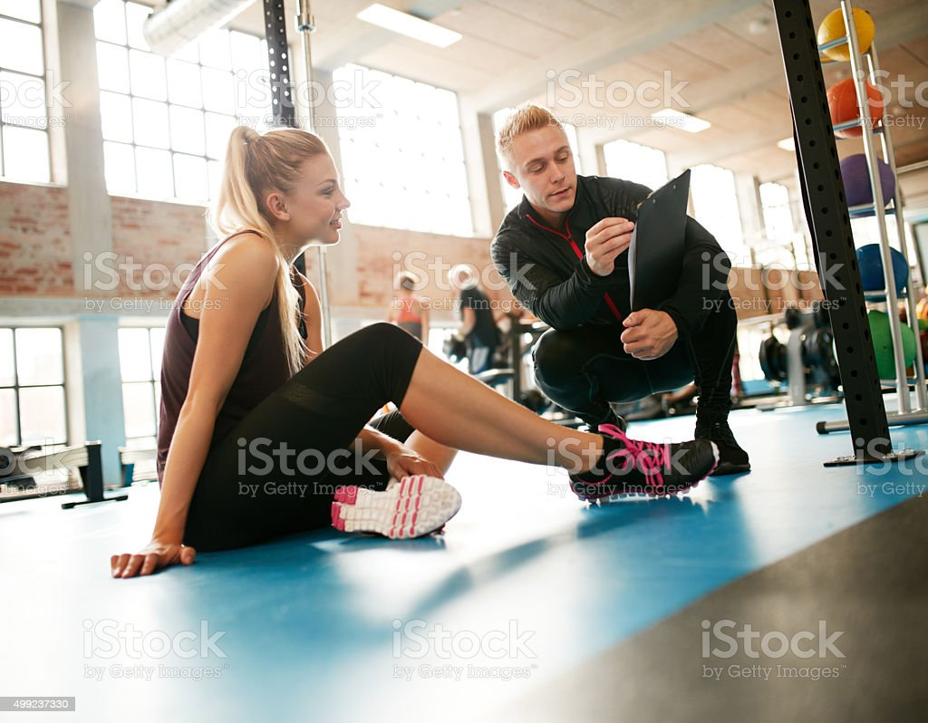Trainer helping woman on her exercises routines Personal trainer helping young woman on her work out routines in gym. Female sitting on floor with her personal trainer showing fitness report on a clipboard. 2015 Stock Photo