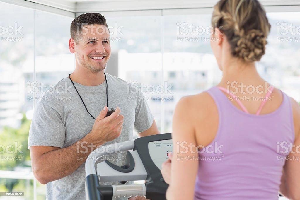Trainer helping woman on treadmill stock photo