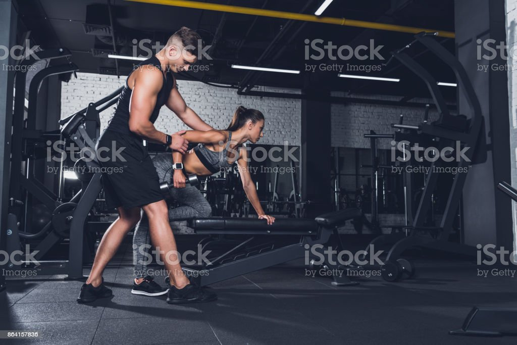 trainer helping woman to exercise with dumbbell royalty-free stock photo