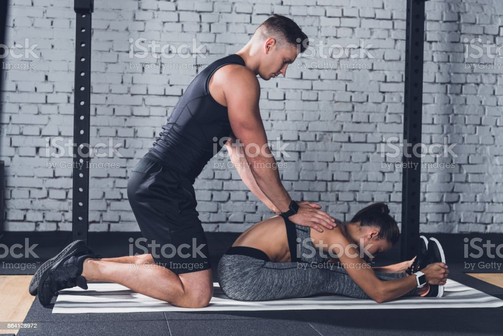 trainer helping woman to stretch royalty-free stock photo