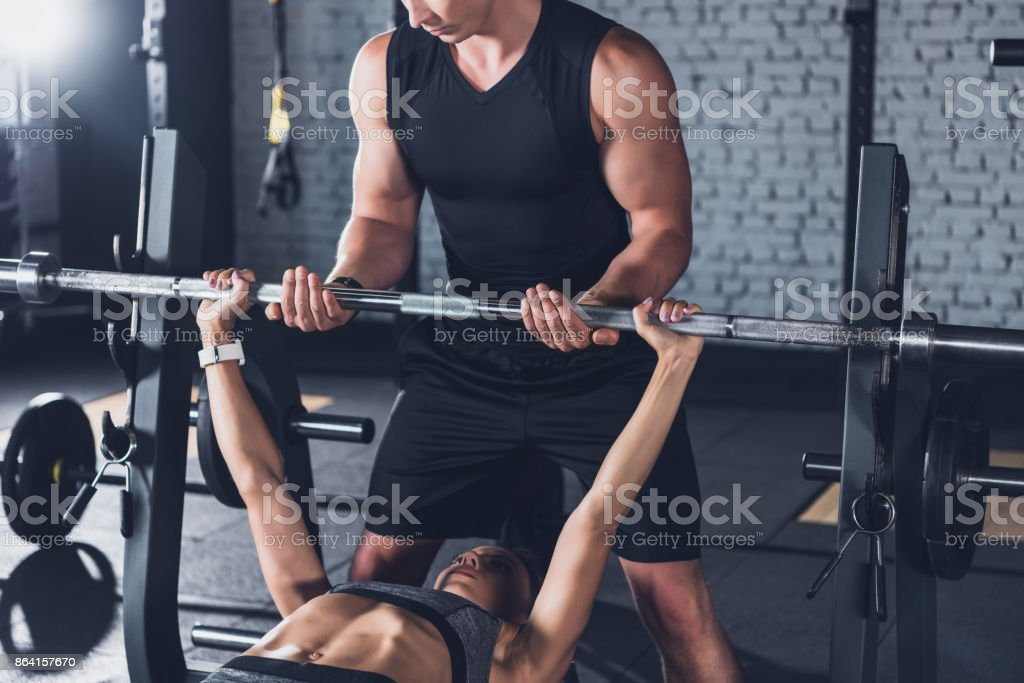 trainer helping woman weightlifting royalty-free stock photo